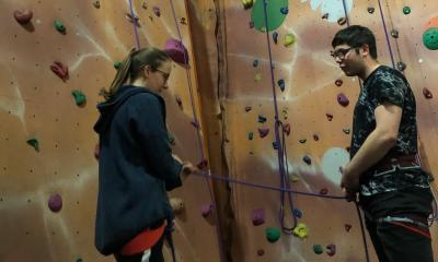 A young person learning to belay with an assistant holding their rope.