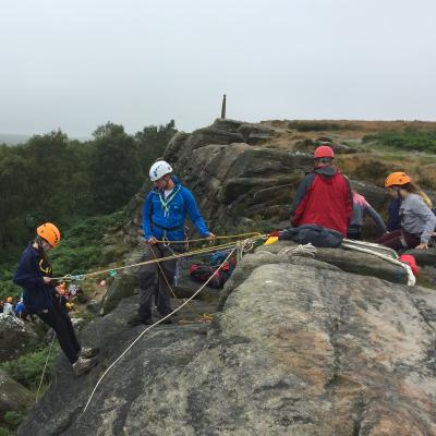 A group abseiling from some rocks, with some trees in the background.