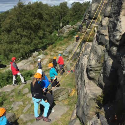 A group of young people climbing at a crag of rough ledges.
