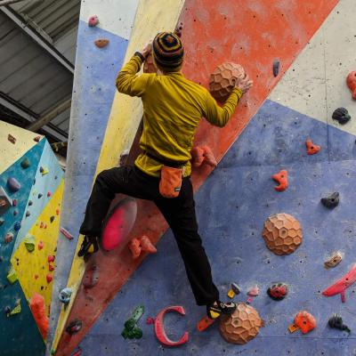 Phill wearing a yellow top, climbing on a multi-coloured bouldering wall.