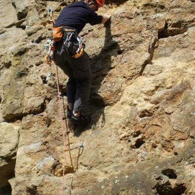 Phill climbing a yellow/brown rock, looking where to put his foot next.