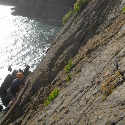 Phill sat at the top of a crag belaying a climber, with the sea in the background.